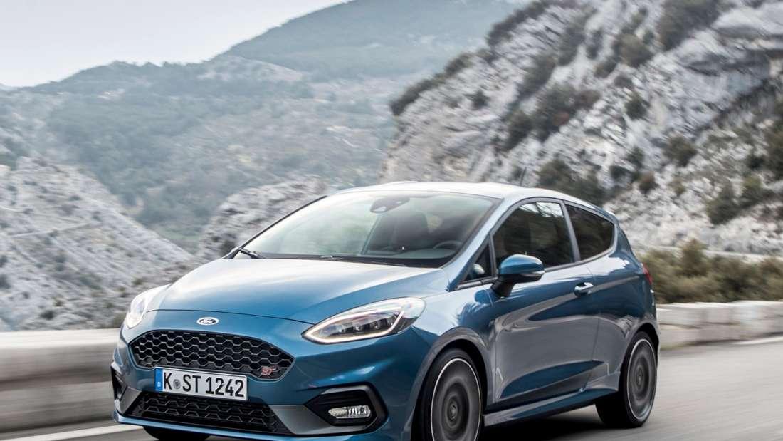 Ein blauer Ford Fiesta ST fährt auf einer Bergstraße.