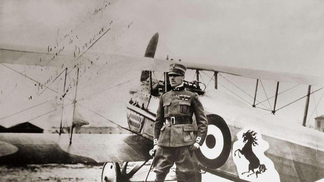 """Franceso Baracca, italienisches Flieger-Ass des Ersten Weltkriegs vor seiner Maschine, die mit dem """"Cavallino Rampante"""" bemalt ist, seinem Familienwappen. Das Logo nutzt Enzo Ferrari später auf Geheiß von Bareccas Mutter als Emblem für seine Fahrzeuge."""