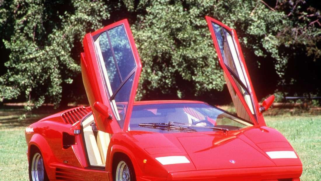 Roter Lamborghini Countach mit offenen Flügeltüren auf einer Wiese stehend