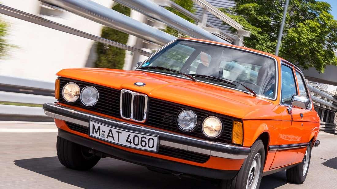Fahraufnahme eines orange-farbenen BMW 3er (E21). Im Hintergrund ist ein weiterer BMW 3er der Generation F30 zu sehen.