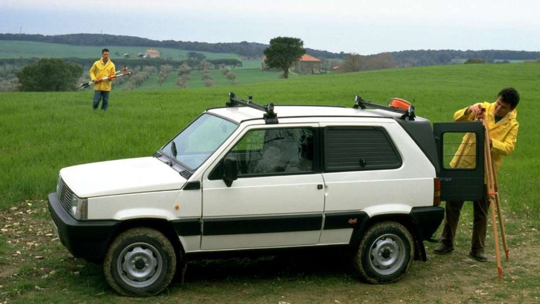 Ein weißer Fiat Panda 4x4 (Allradantrieb) der ersten Generation (Typ 141) steht auf einer Wiese.