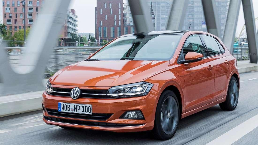 Ein orangefarbener VW Polo VI (Typ AW) fährt über eine Brücke.