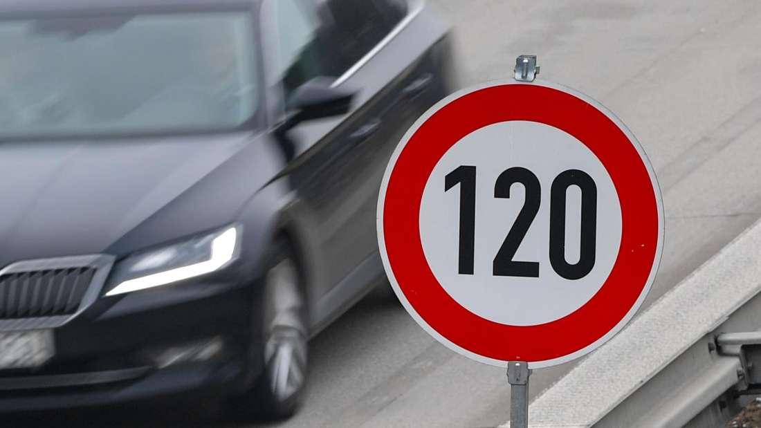 """Ein Auto fährt an einem Verkehrschild """"Tempo 120"""" vorbei."""
