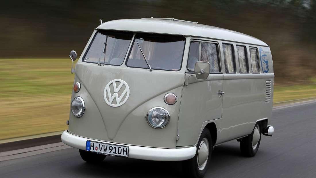 Ein grauer VW Bus (Bulli) der ersten Generation (T1) fährt auf einer Landstraße.