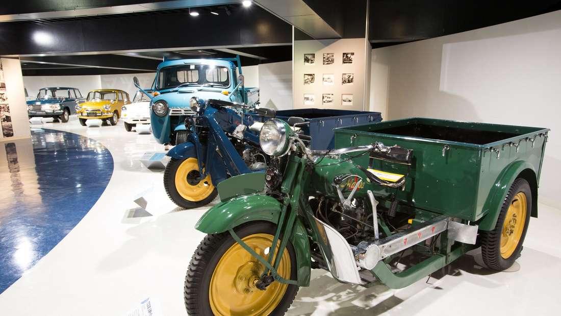 Ein dreirädriges Gefährt von Mazda – ein Mazdago/Mazda Go – steht in einer Ausstellungshalle.