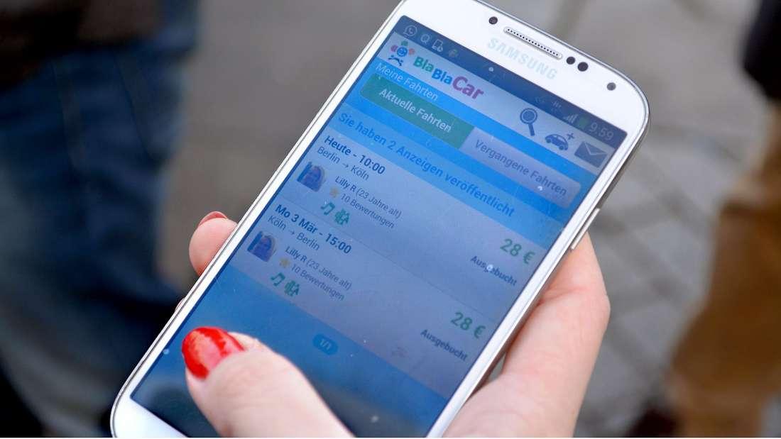 Eine Frau bedient ihr Handy und informiert sich dabei über die App BlaBlaCar.