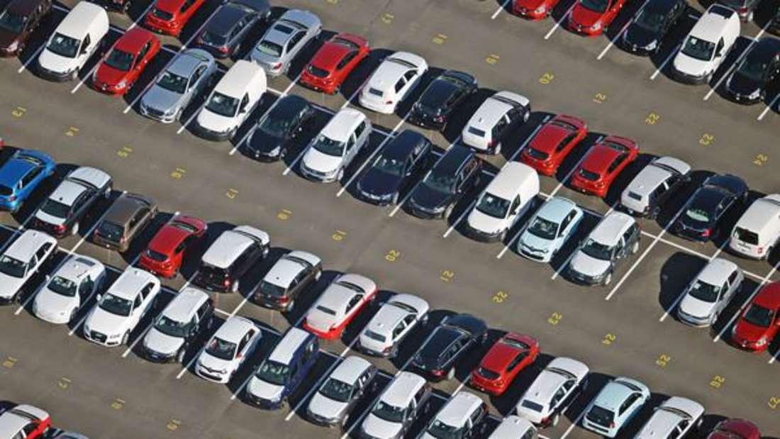 Mehrere Autos stehen in Reihen auf einem Parkplatz.