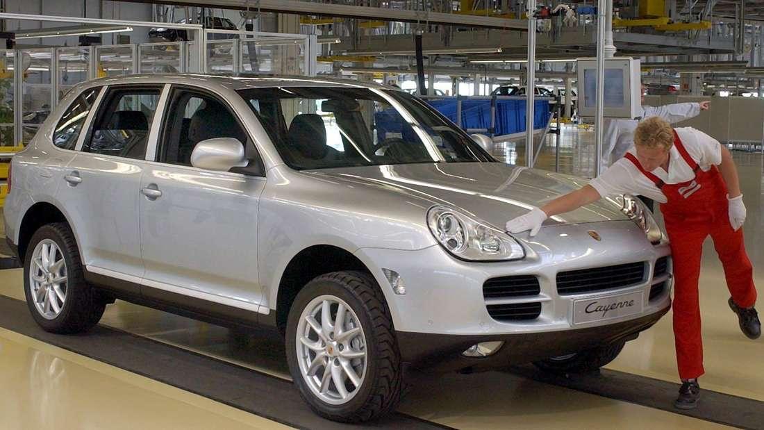 Ein Mitarbeiter schließt am 20.08.2002 am Fließband im Porsche-Werk in Leipzig die Motorhaube vom ersten Geländewagen Cayenne.