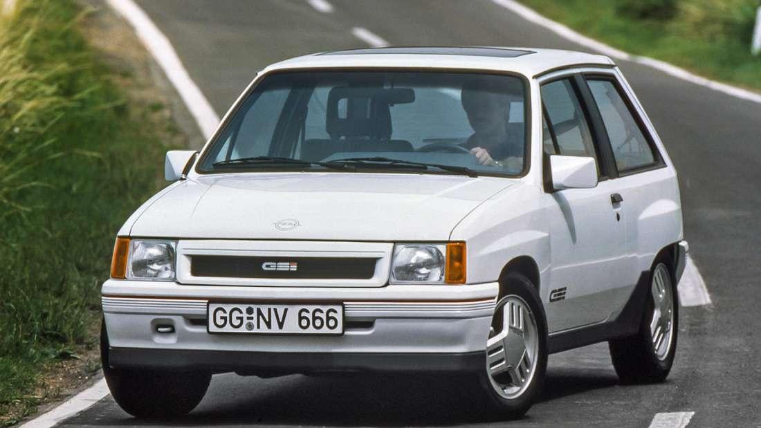 Fahraufnahme eines weißen Opel Corsa GSI der ersten Generation (Opel Corsa A).