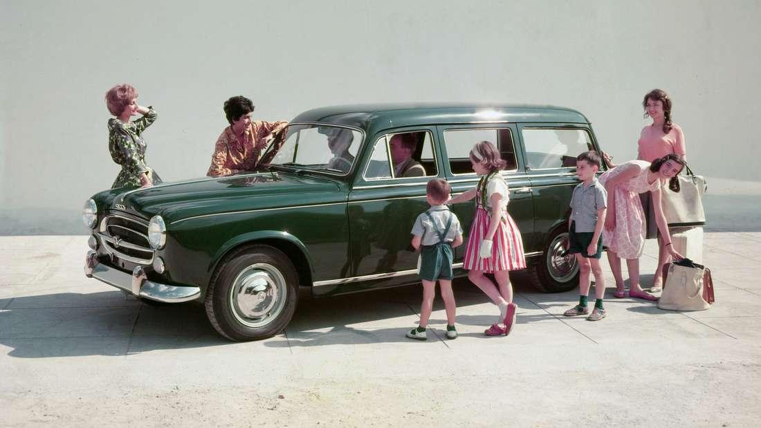 Frauen und Kinder scharen sich um einen grünen Peugeot 403.