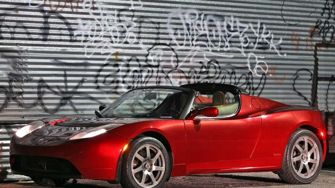 Roter Tesla Roadster vor einer Wand mit Graffiti
