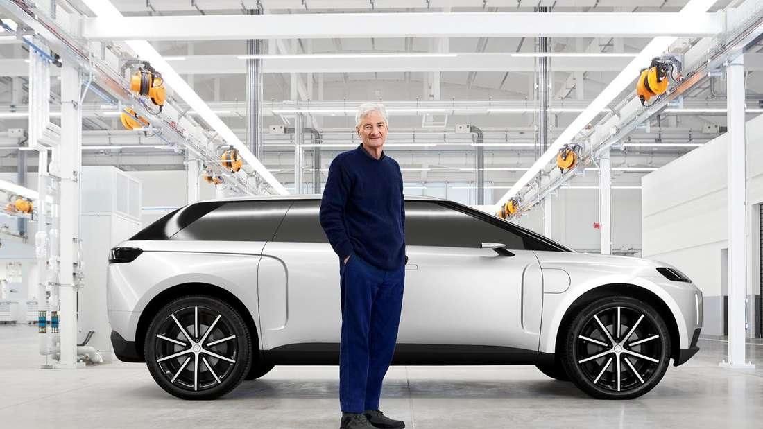 James Dyson steht in einer Fabrikhalle vor einem weißen Dyson EV.