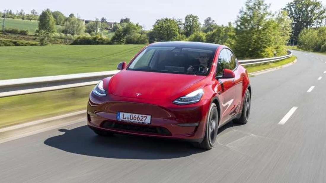 Tesla Model Y fahrend auf einer Landstraße.
