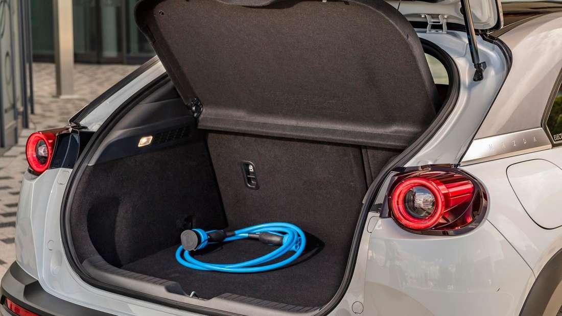 Ein blaues Ladekabel liegt im geöffneten Kofferraum eines Mazda MX-30.
