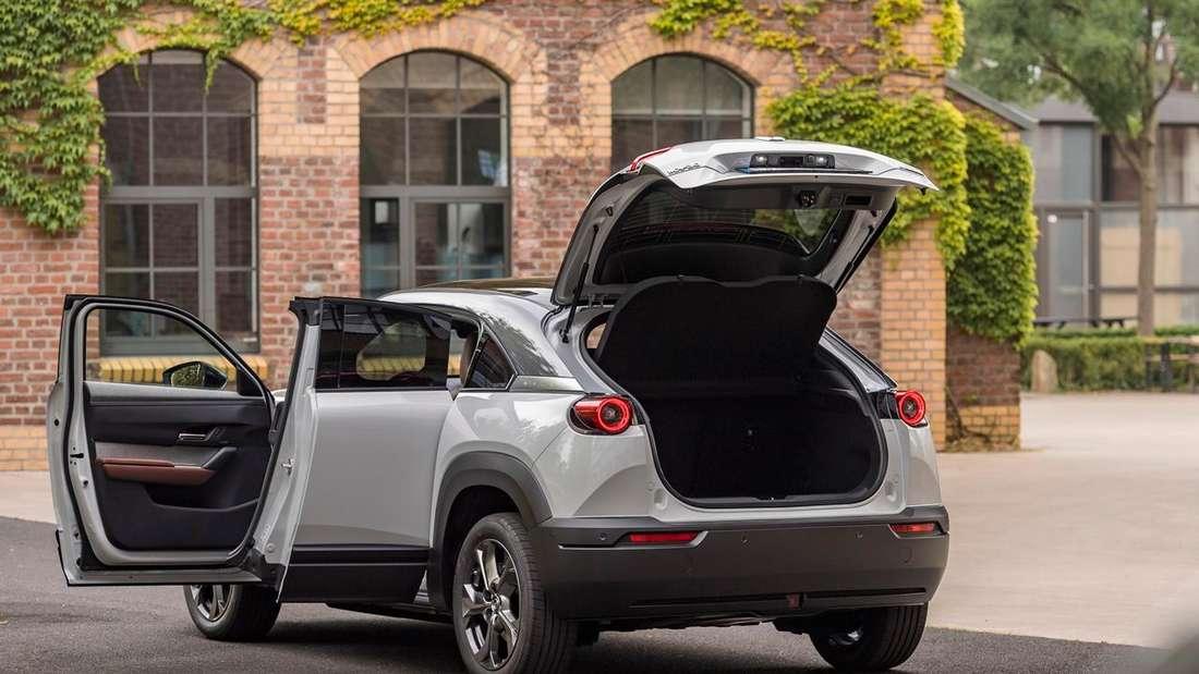 Ein silberfarbener Mazda MX-30 mit geöffnetem Kofferraum und geöffneten Türen.