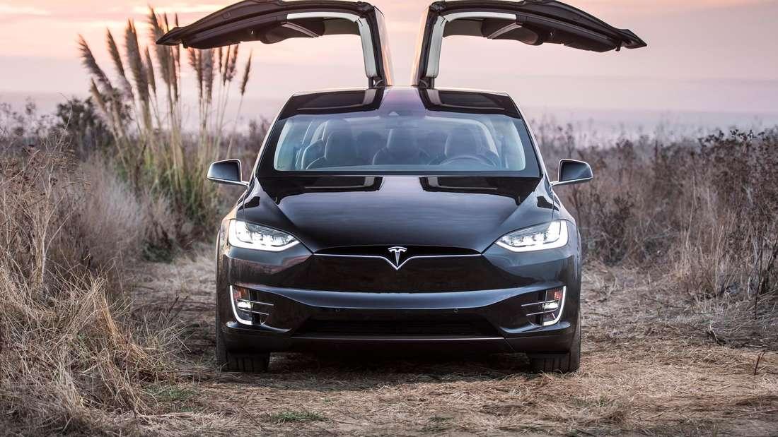 Frontale Aufnahme eines Tesla Model X der ersten Generation mit geöffneten Flügeltüren.