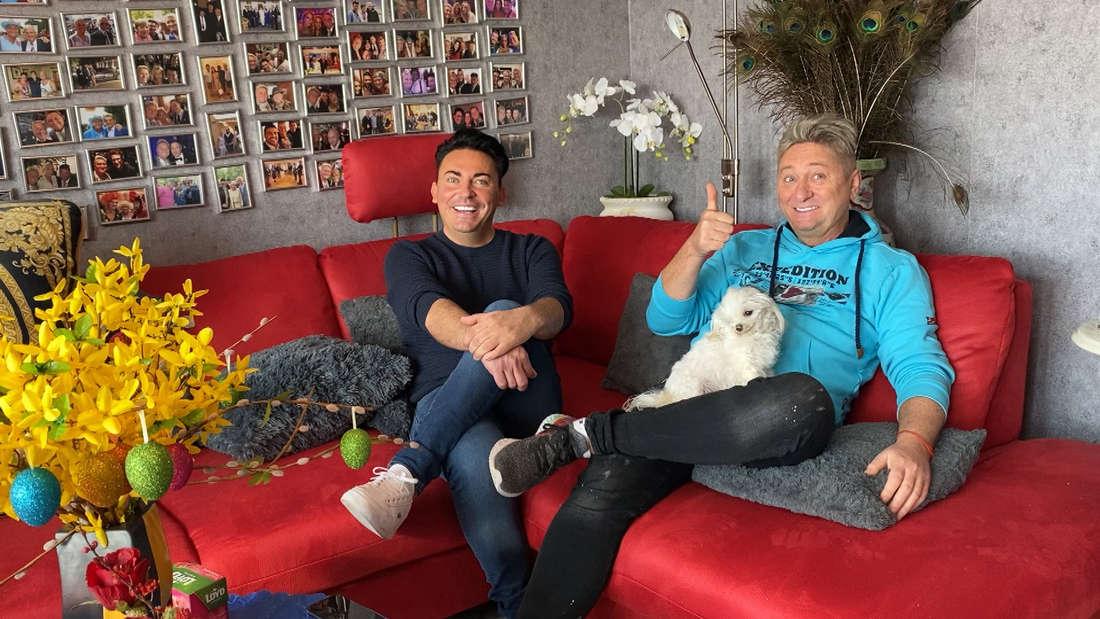 Matthias Mangiapane (links) und sein Ehemann Hubert Fella sitzen auf einem roten Sofa.