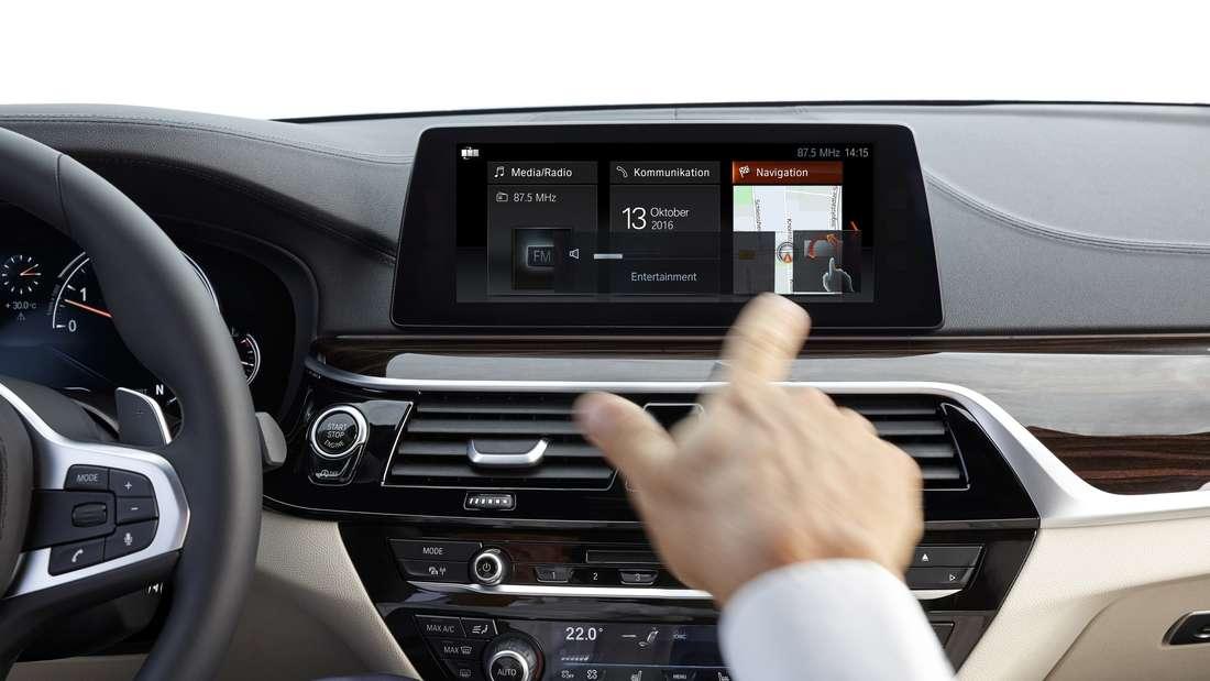 Ein Hand bewegt sich vor einem BMW-Navi-Display.