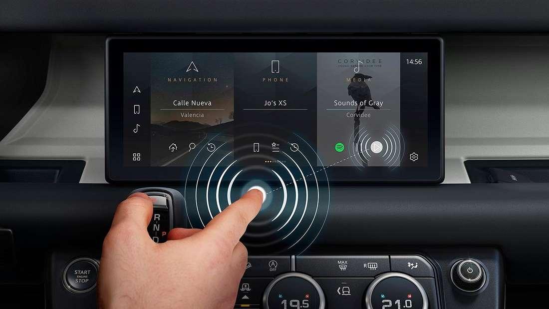 Jaguar Land Rover: Hand mit ausgestrecktem Zeigefinger vor einem Infotainment-Display