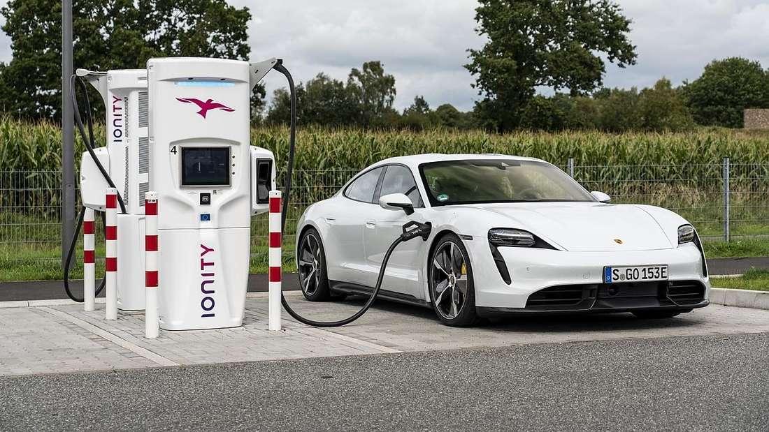 Ein weißer Porsche Taycan tankt Strom an einer Ionity-Schnellladesäule.