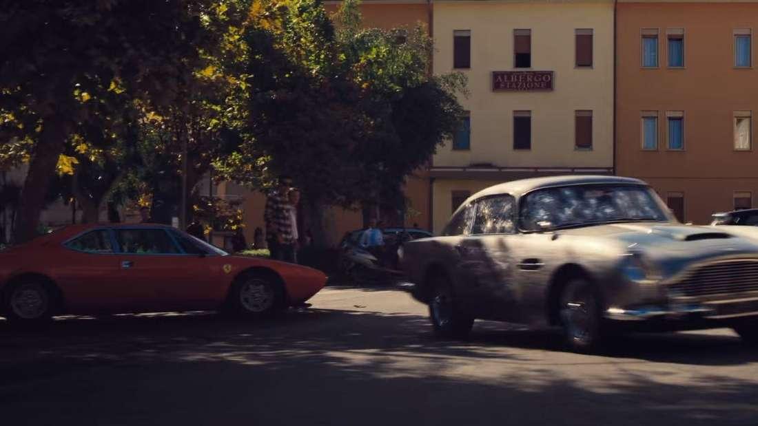 """Screenshot aus """"James Bond 007: Keine Zeit zu sterben"""". Aston Martin DB5 fahrend. Ferrari Dino 308 GT4 am linken Bildrand."""