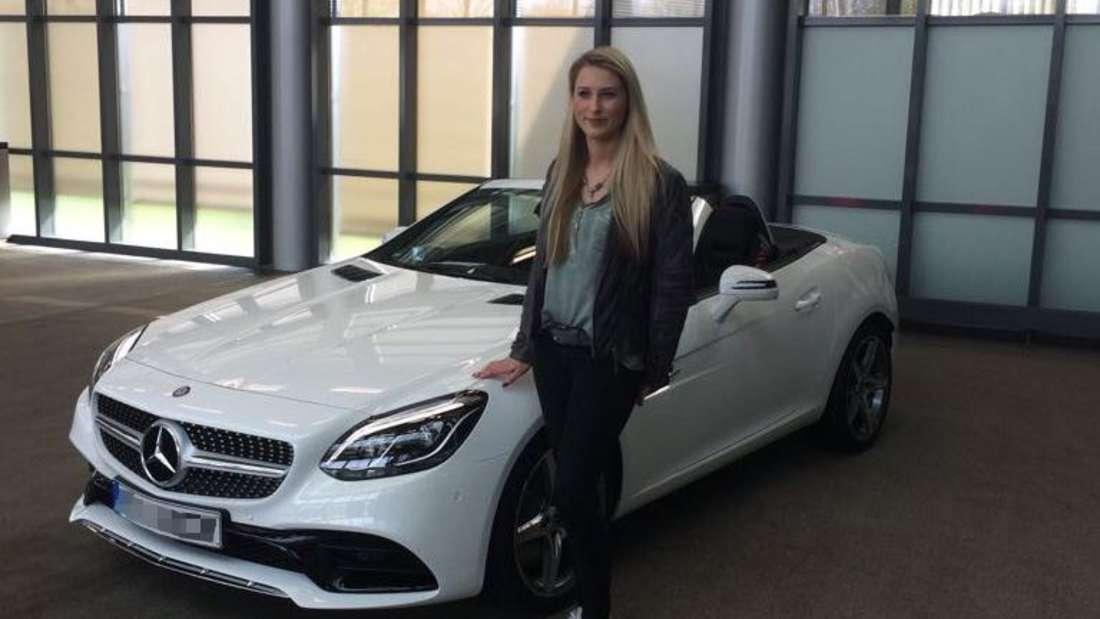 Romina Kohlisch steht vor ihrem weißen Mercedes-Benz SLC 200.