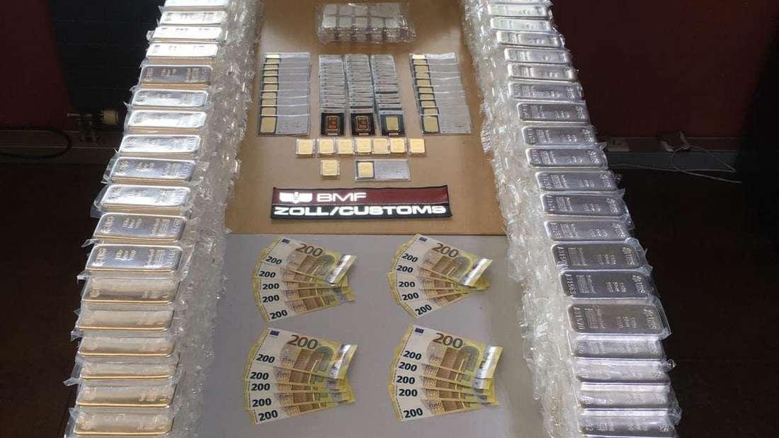 Beschlagnahmte Gold- und Silberbarren liegen auf einem Tisch.