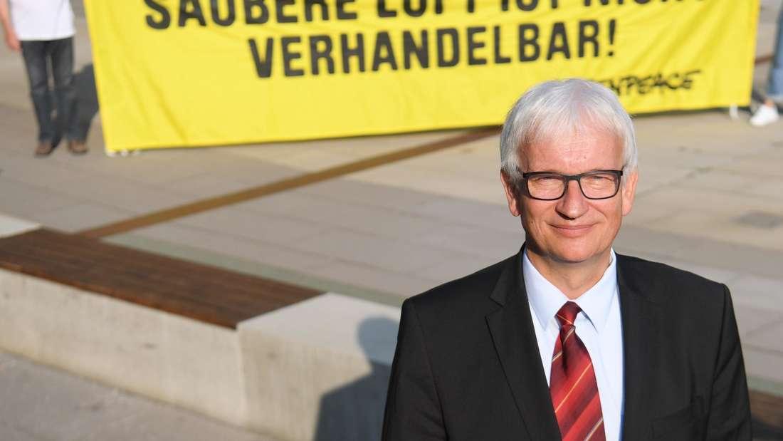 """Jürgen Resch, Geschäftsführer der """"Deutschen Umwelthilfe"""" (DUH), vor einem Greenpeace-Plakat mit der Aufschrift """"Saubere Luft ist nicht verhandelbar!""""."""