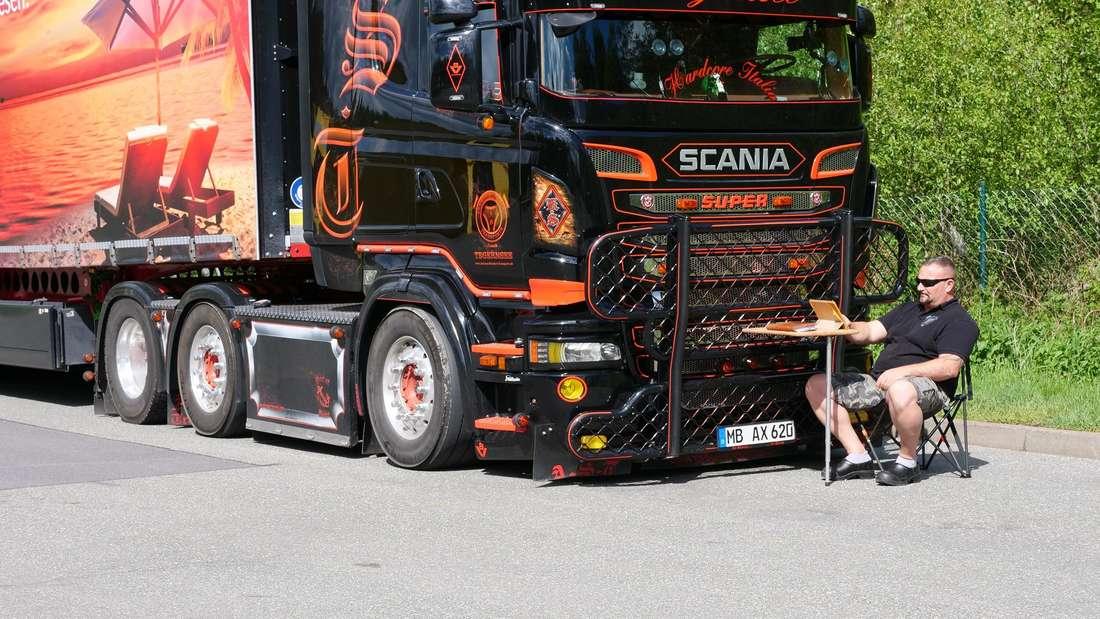 Andreas Schubert sitzt an einem Tisch vor seinem Scania-Truck.