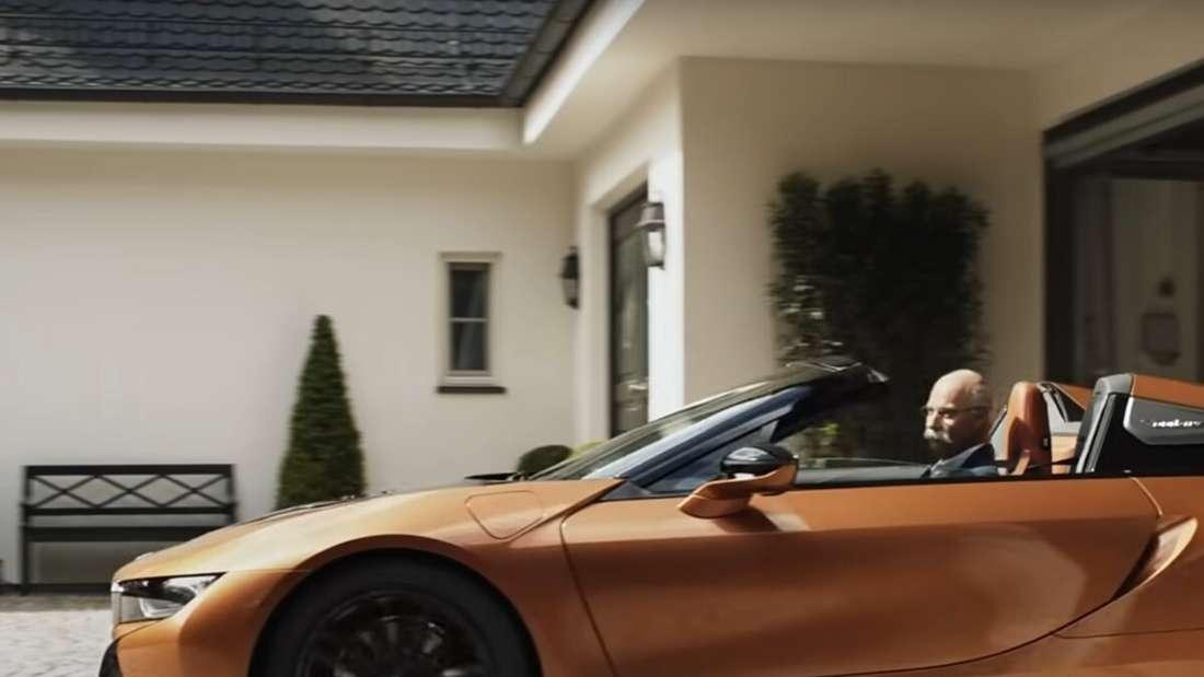 Das Dieter-Zetsche-Double braust in einem BMW i8 aus der Garage.
