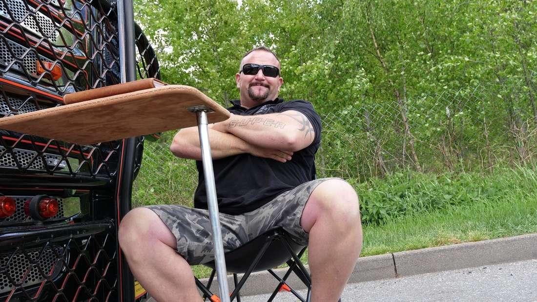 Lkw-Fahrer Andreas Schubert posiert vor seinem Truck.