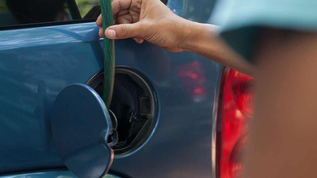 Ein Mann versucht, mit einem Schlauch zuvor eingefülltes Benzin aus einem Tank zu bekommen.