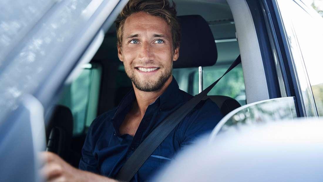 Ein Mann lacht aus dem geöffneten Fenster eines Autos. (Symbolbild)