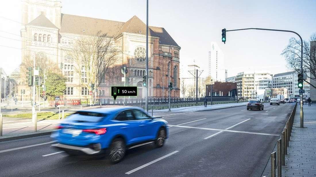 Ein blauer Audi Q2 fährt auf eine Ampel zu.