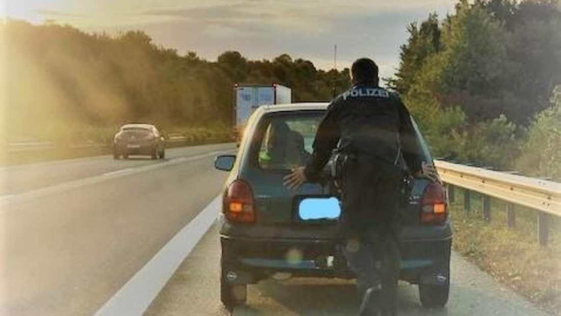 Ein Polizist schiebt einen Opel Corsa auf dem Standstreifen einer Autobahn.