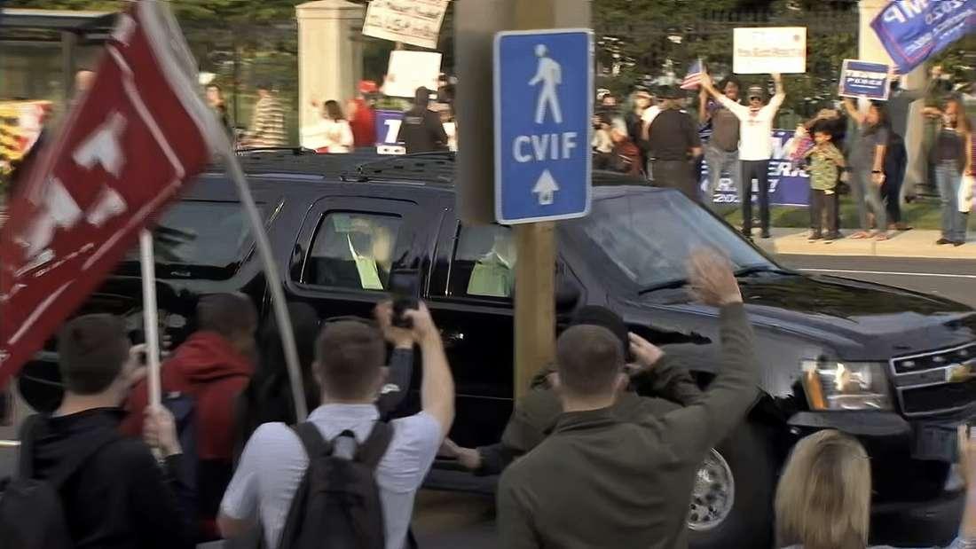 US-Präsident Donald Trump winkt aus einem gepanzerten Chevrolet Suburban seinen Fans zu.