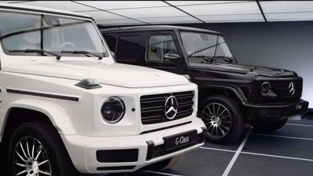 Ein weiße und eine schwarze G-Klasse von Mercedes-Benz stehen in einem Showroom.