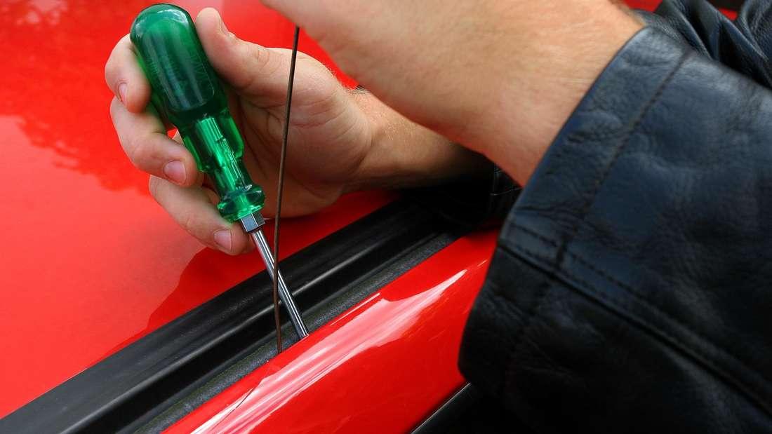 Eine Autotür wird mit Hilfe eines Schraubenziehers geöffnet. (Symbolbild)