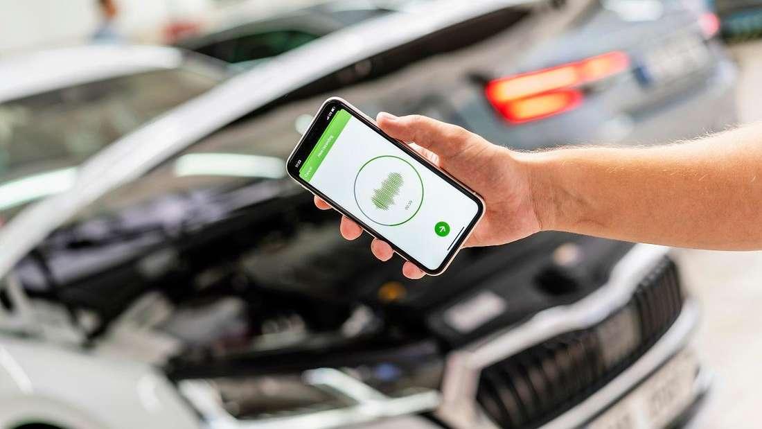 Ein Smartphone wird vor den geöffneten Motorraum eines Škoda gehalten.