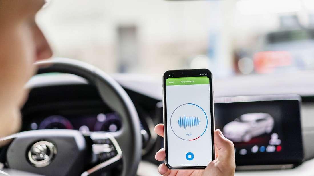 Ein Smartphone wird vom Fahrer eines Škoda im Innenraum hochgehalten.