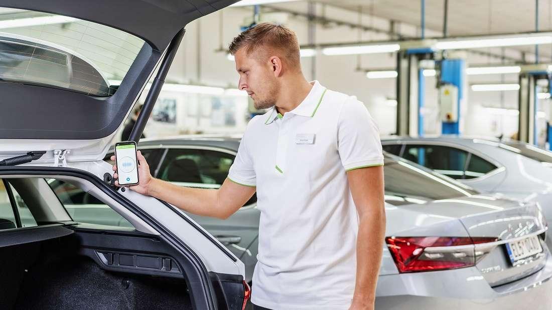 Ein Servicetechniker steht mit einem Smartphone in der Hand vor dem geöffneten Kofferraum eines Škoda.