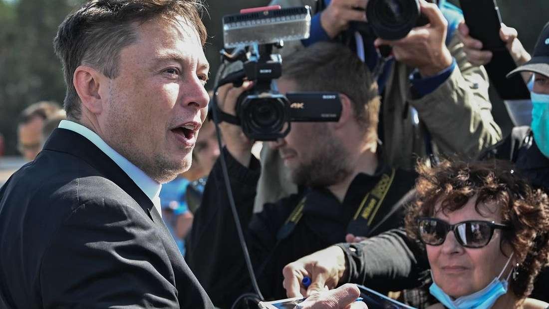 Tesla-Chef Elon Musk steht auf der Baustelle der Tesla Gigafactory im brandenburgischen Grünheide und gibt Autogramme.