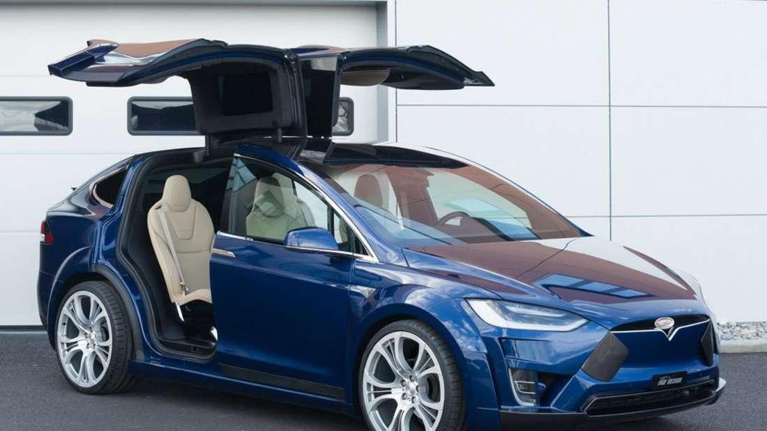 Ein Tesla Model X steht vor einer Garage.