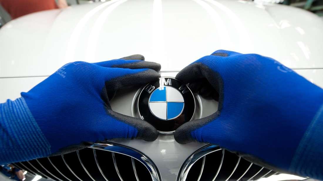 Ein BMW-Emblem wird im BMW-Werk Regensburg auf ein Fahrzeug der BMW 3er Reihe geklebt.
