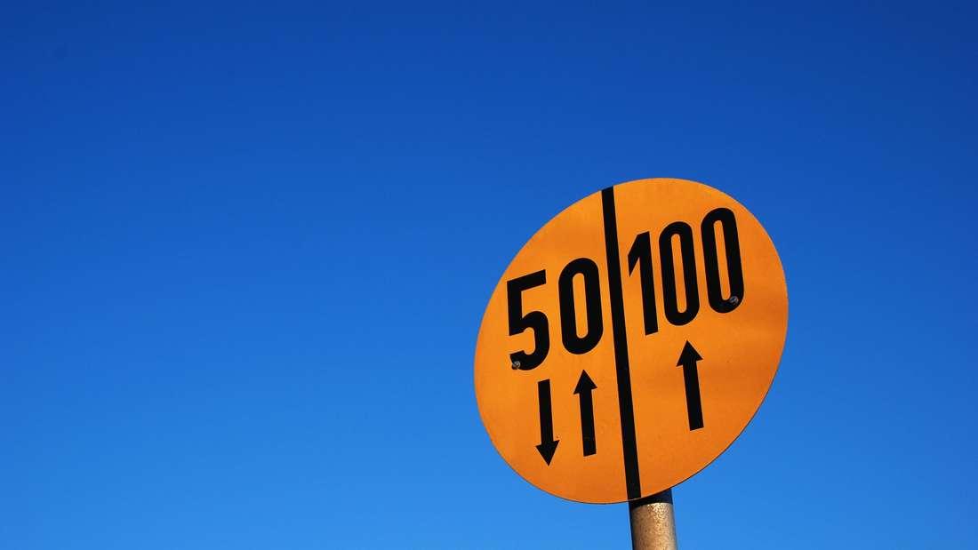 Ein kreisrundes oranges MLC-Verkehrszeichen steht vor blauem Himmel.