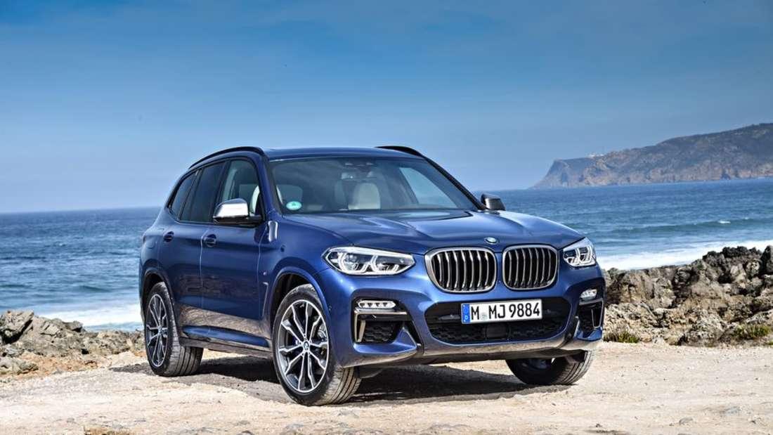Ein blauer BMW X3 steht vor dem Hintergrund des Meeres.
