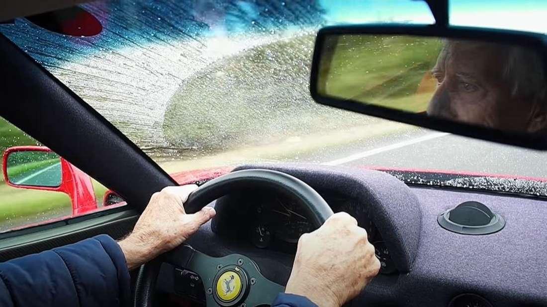 Ein älterer Herr steuert einen Ferrari F40 und ist im Rückspiegel zu sehen.