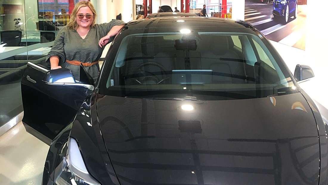 Die Radiomoderatorin Annabelle Brett aus dem australischen Canberra steht in der geöffneten Tür ihres Tesla Model 3.