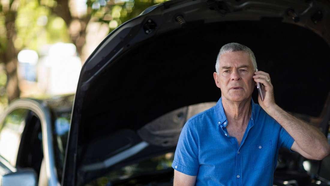 Ein älterer Mann steht vor der geöffneten Motorhaube seines Autos und telefoniert.