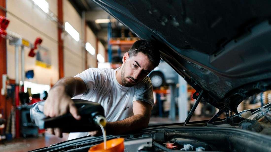 Ein Mann füllt in einer Werkstatt mit einem Trichter Öl in den Motor eines Autos.